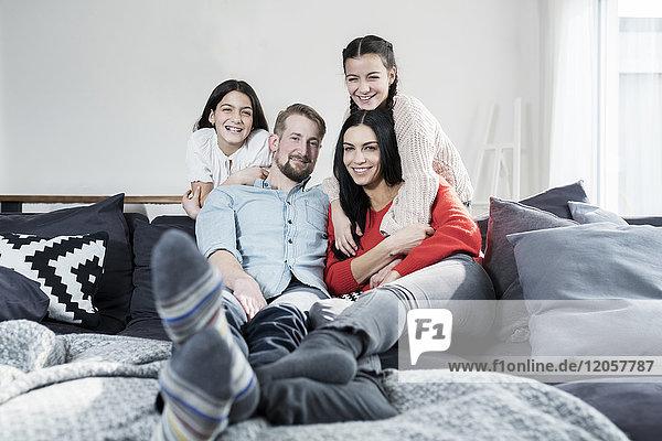 Familienporträt der Eltern und Zwillingstöchter auf Sofa im Wohnzimmer