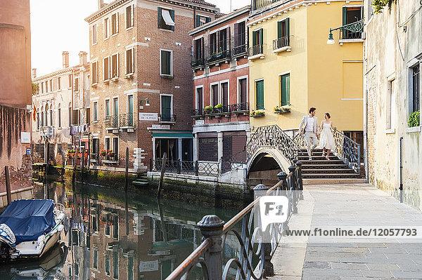 Italien  Venedig  Brautpaar  das auf einer kleinen Brücke läuft