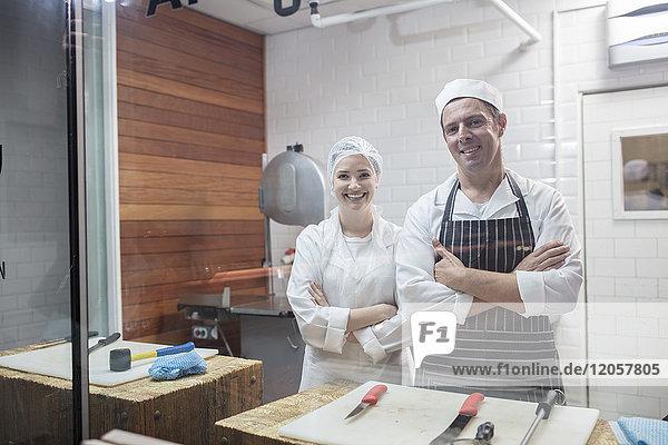 Porträt eines lächelnden Mannes und einer lächelnden Frau in der Metzgerei