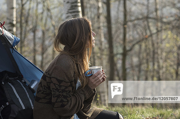 Frau beim Zelten im Wald