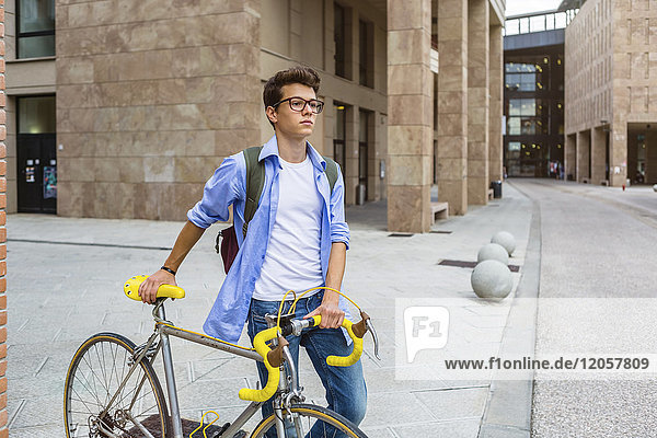 Junger Mann schiebt sein Fahrrad