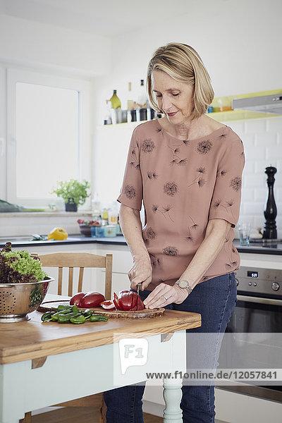 Reife Frau bei der Zubereitung eines Salats in der Küche