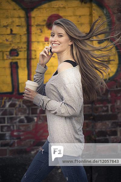 Porträt der lachenden Frau mit Kaffee zum Telefonieren