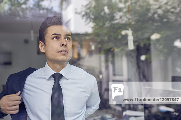 Porträt eines jungen Geschäftsmannes hinter Glasscheibe im Büro beim Anziehen seiner Jacke
