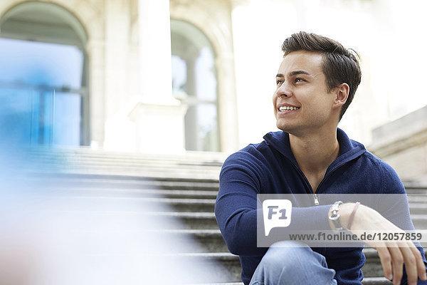 Porträt eines lachenden jungen Mannes  der auf einer Treppe sitzt.