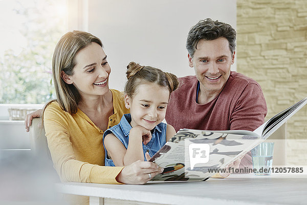 Happy family at home looking at picture book