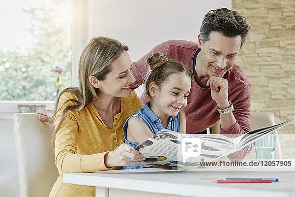 Glückliche Familie zu Hause beim Betrachten des Bilderbuches