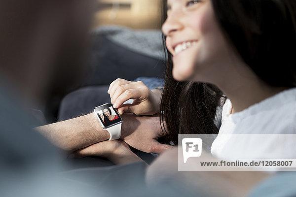 Tochter und Vater mit smartwatch mit Mutter winkend