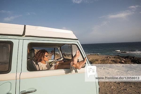 Spanien  Teneriffa  Frau sitzend mit Füßen oben im Van am Meer geparkt