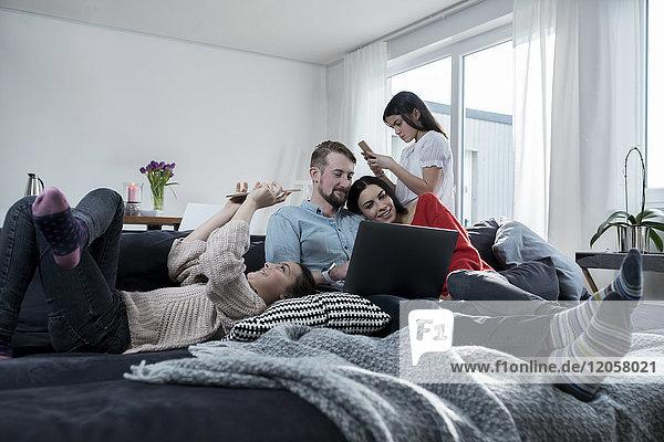 Eltern und Zwillingstöchter auf dem Sofa mit tragbaren Geräten
