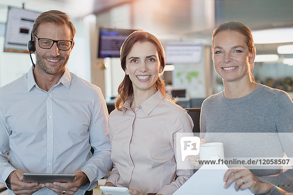 Portrait smiling  confident business people with digital tablet and coffee in office