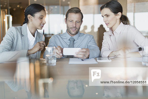 Business people using cell phone in conference room meeting
