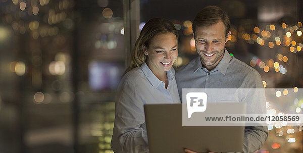 Smiling businessman and businesswoman working late at laptop in office at night