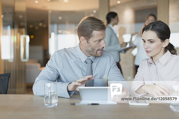 Businessman and businesswoman using digital tablet  talking in conference room meeting