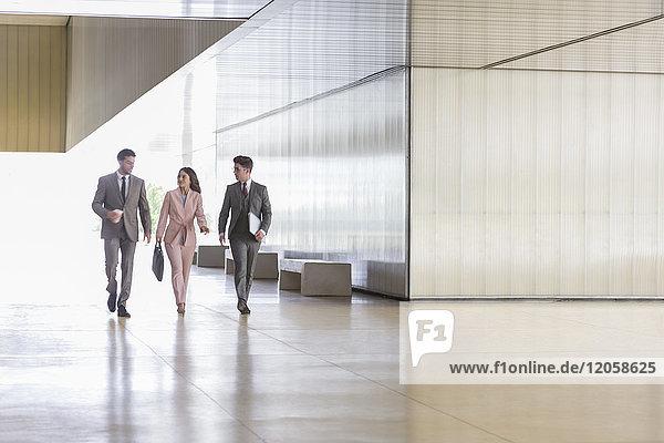 Geschäftsleute beim Gehen und Sprechen im modernen Büroflur