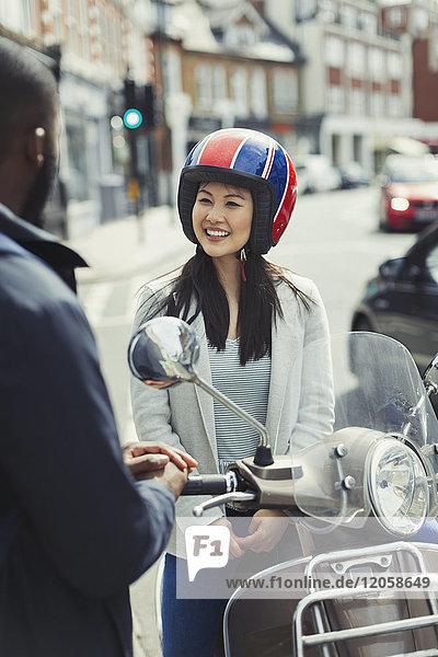 Lächelnde junge Frau im Helm auf dem Motorroller  im Gespräch mit einem Freund in der Stadt.
