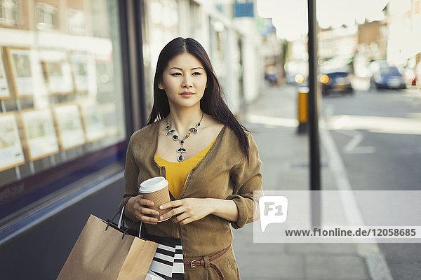 Junge Frau geht mit Kaffeetasse und Einkaufstaschen an der Schaufensterfront entlang.