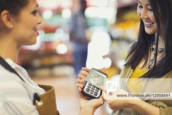 Kundin mit Kreditkarte bei kontaktloser Bezahlung im Geschäft