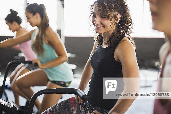Lächelnde junge Frau auf einem elliptischen Fahrrad in der Übungsklasse