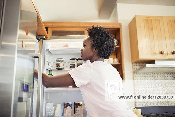 Frau greift in den Kühlschrank in der Küche