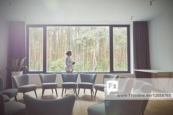 Nachdenkliche Frau schaut aus dem Fenster auf Bäume im Gruppentherapieraum.