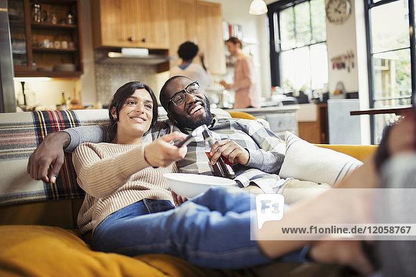 Lächelndes junges Paar beim Fernsehen  Bier trinken und Popcorn essen auf dem Wohnzimmersofa