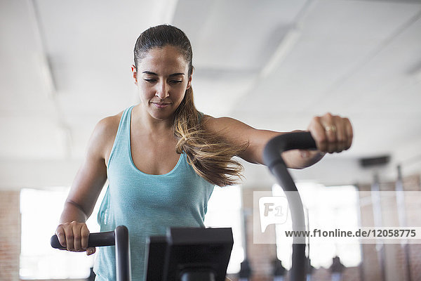 Fokussierte junge Frau mit Ellipsentrainer im Fitnessstudio