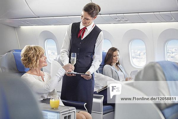 Flugbegleiterin  die der Frau in der ersten Klasse im Flugzeug Champagner serviert.