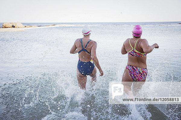 Weibliche Freischwimmerinnen beim Laufen und Plantschen im Meer