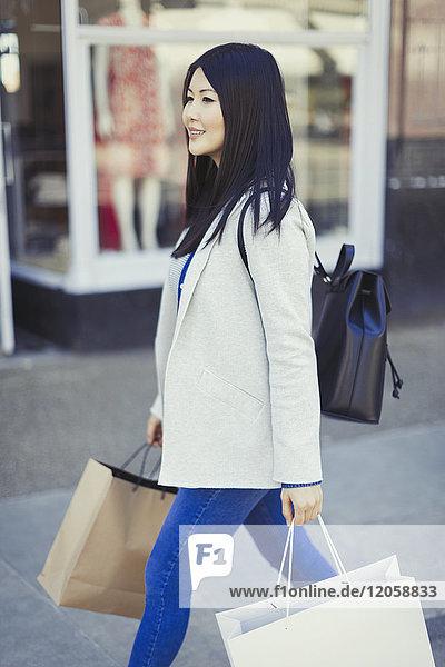 Junge Frau geht mit Einkaufstaschen an der Schaufensterfront entlang