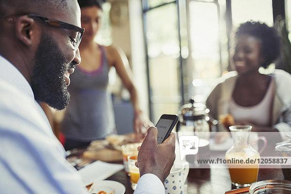 Junger Mann SMS mit Smartphone am Küchentisch