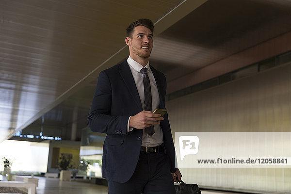 Geschäftsmann zu Fuß mit Smartphone in der Büro-Lobby