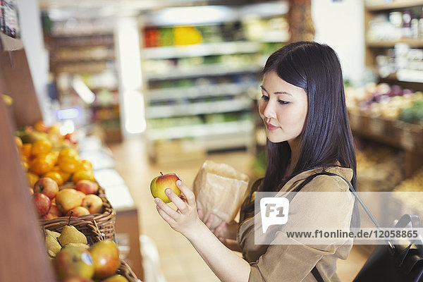 Junge Frau beim Einkaufen  Untersuchung von Äpfeln im Lebensmittelladen