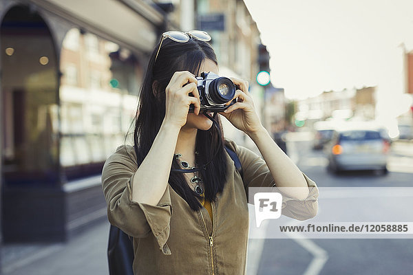 Young female tourist photographing with camera on urban street
