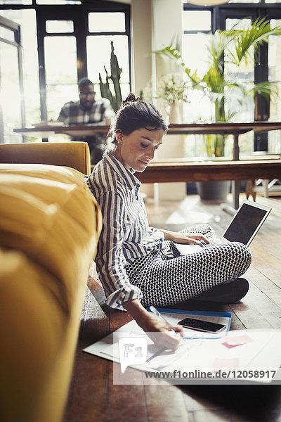 Female freelancer working at laptop  taking notes on living room floor
