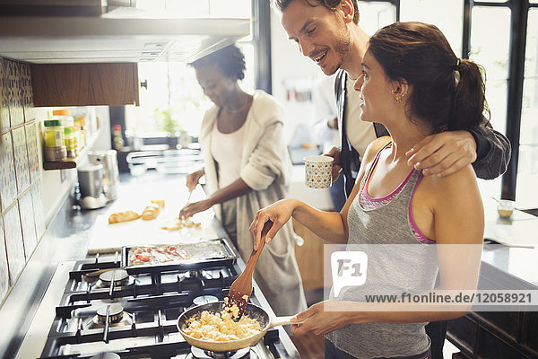 Junges Paar beim Kochen von Rühreiern auf dem Herd in der Küche