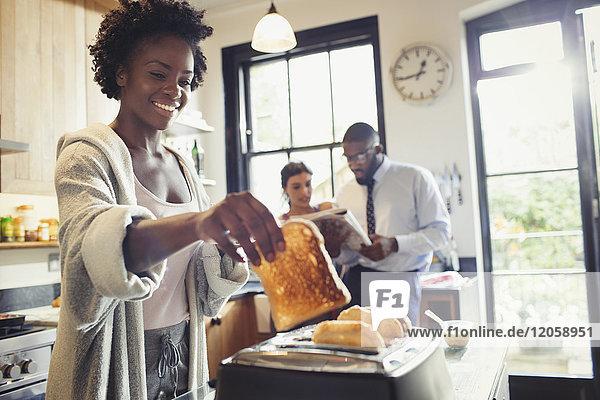 Lächelnde Frau toastet Brot im Toaster in der Küche