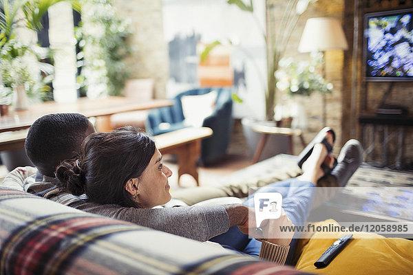 Zärtliches junges Paar beim Fernsehen auf dem Wohnzimmersofa