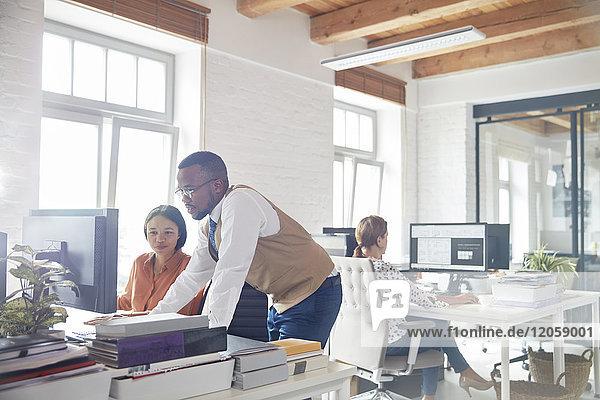 Geschäftsmann und Geschäftsfrau mit Computer im Büro