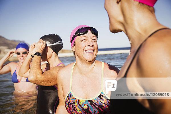 Lachende Schwimmerinnen sprechen im sonnigen Ozean