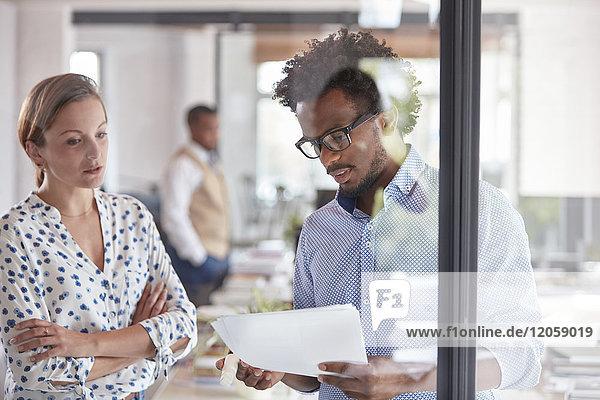 Geschäftsmann und Geschäftsfrau besprechen Papierkram im Büro