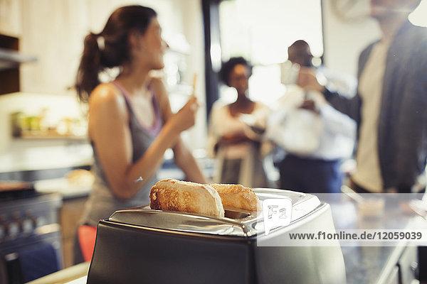 Freund Zimmergenossen sprechen hinter Toast in Toaster in der Küche