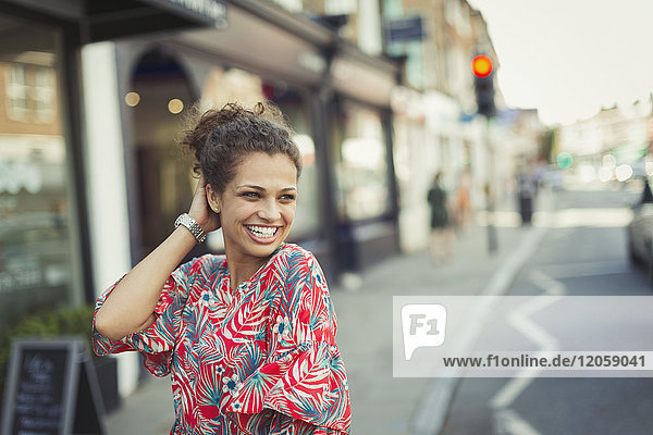 Portrait confident  laughing young woman on urban street