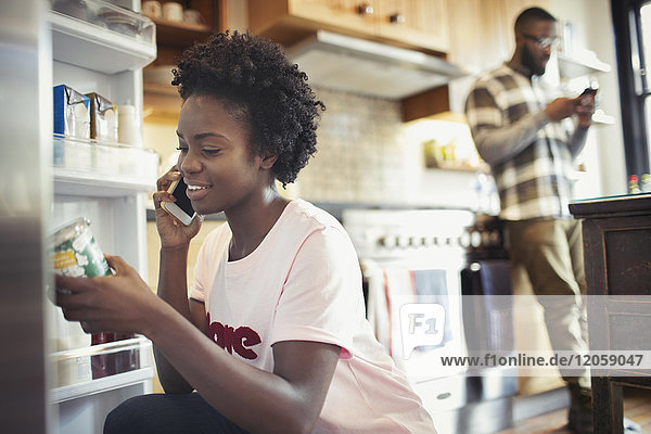 Frau spricht auf Smartphone  liest Etikett auf Glas im Kühlschrank in der Küche