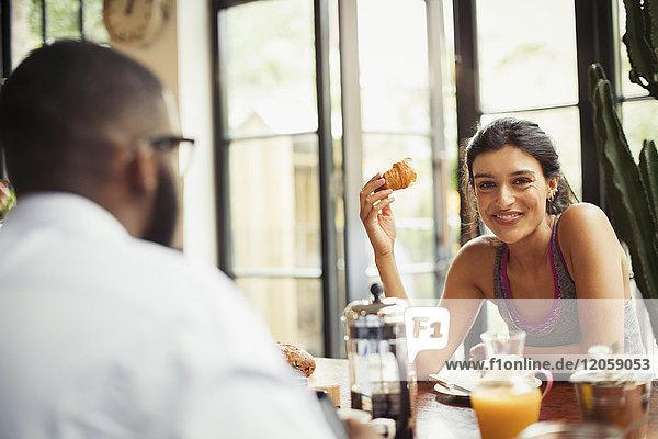Portrait lächelnde junge Frau genießt Croissant und Kaffee im Cafe