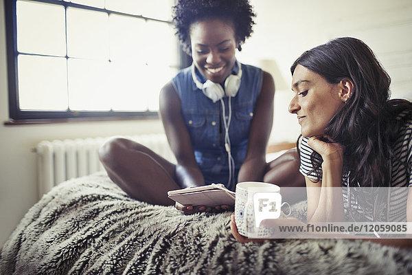 Frauen mit Kopfhörer und Kaffee mit digitalem Tablett auf dem Bett