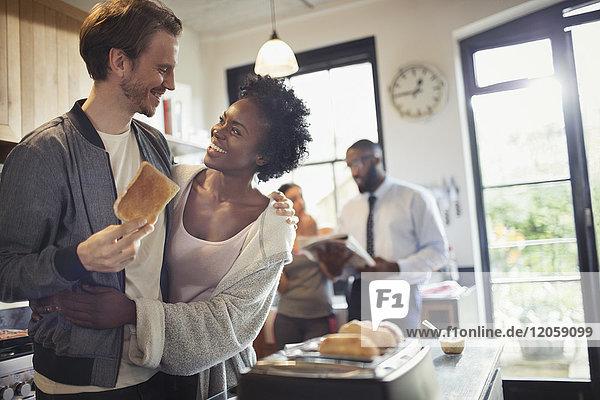 Zärtliche Paarumarmung und Toastessen in der Morgenküche