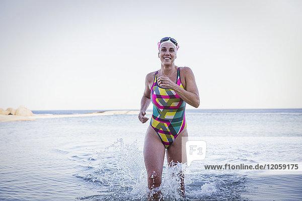 Portrait lächelnde  selbstbewusste Schwimmerin beim Laufen und Plantschen in der Meeresbrandung