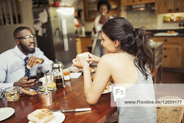 Ein Paar trinkt Kaffee und frühstückt am Tisch.