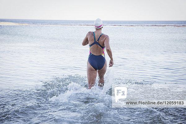 Weibliche Freiwasserschwimmerin  die in die Meeresbrandung läuft.